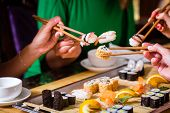 image of sushi  - Young people eating sushi in Asian restaurant - JPG