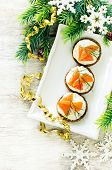 pic of canapes  - canape with salmon and cream cheese with dill for Christmas on a light woody background - JPG
