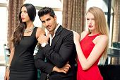 picture of charming  - Portrait of a handsome fashionable man with two charming women posing - JPG
