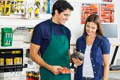 stock photo of hardware  - Worker accepting payment through smartphone from woman in hardware store - JPG