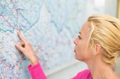 pic of orientation  - Woman orientating herself on the public transport map pointing on her final destination. ** Note: Shallow depth of field - JPG