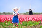 foto of national costume  - Adorable curly toddler girl wearing Dutch traditional national costume dress and hat playing in a field of blooming tulips next to a windmill in Amsterdam region Holland Netherlands - JPG