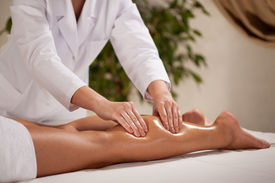 picture of calf  - Horizontal view of masseur massaging woman - JPG