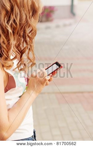 beautiful girl with curly hair standing on the street in phone in hand, sends an SMS message reads