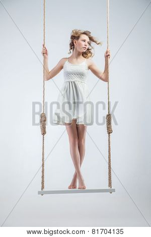 Young bare-footed girl on swing looking left.