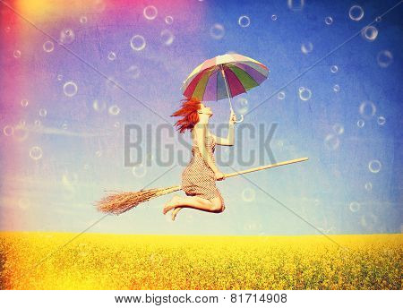 Red-haired Girl Fly With Umbrella Over Rape Field And Bubbles Around.
