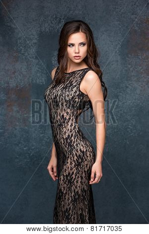 Beautiful young brunette woman with her hair posing in a tracery dress. Studio, on gray background