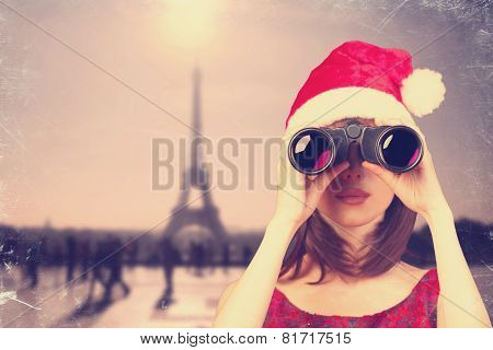 Girl With Binocular And Christmas Hat And Parisian Background.