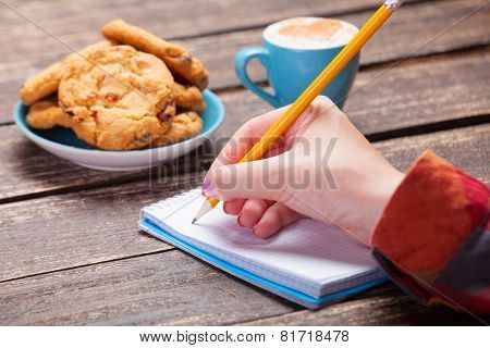 Female Hand Writing Something In Note Near Cookie And Cup Of Coffee.