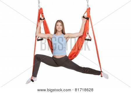 Young woman doing anti-gravity aerial yoga in hammock on a seamless white background.