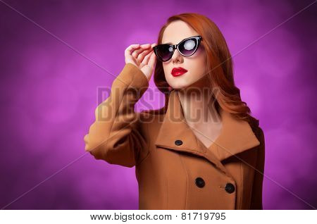 Redhead Women In Coat On Vilolet Background.