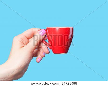 Hand Holding Red Cup On Blue Background
