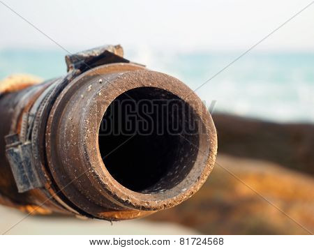 Sewage pipe is rusty and the background is the sea