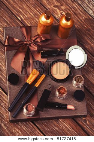 Cosmetics And Gift Box On Wooden Table.