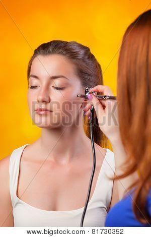 Visagist Making Makeup For Model With Aerograph