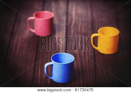 Three Color Cups On Woodent Table.