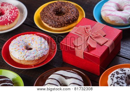 Donuts And Gift On Wooden Table.