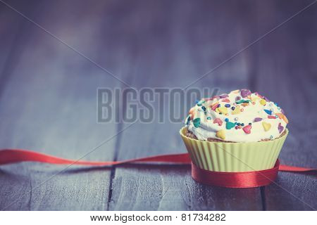 Cupcake And Bow On Wooden Table.