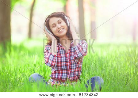 Indian Girl With Headphones In The Park.