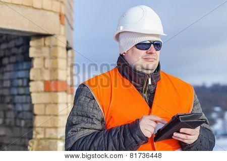 Worker with tablet PC near unfinished building