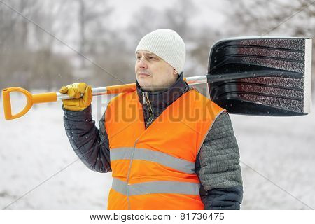 Worker with snow shovel in winter