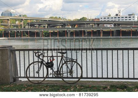 Bicycle Against A Railing Along The Waterfront In Portland, Oregon