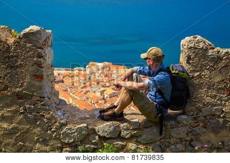 Traveller Sitting On The Stone Fence