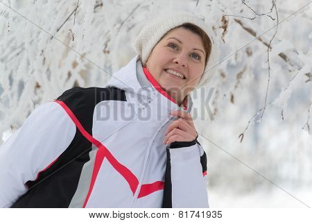 middle-aged woman in a birch forest in winter