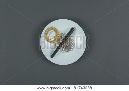 Pen, Rubber Bands And Paper Clips On A Plate