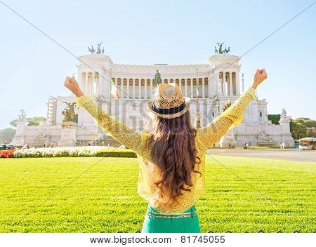 Young Woman On Piazza Venezia In Rome, Italy Rejoicing. Rear View