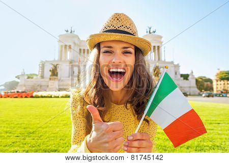 Portrait Of Happy Young Woman Showing Italian Flag And Thumbs Up On Piazza Venezia In Rome, Italy