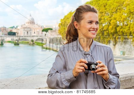 Portrait Of Happy Young Woman With Photo Camera While On Bridge