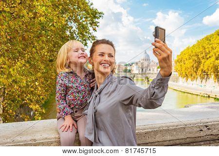 Happy Mother And Baby Girl Making Selfie On Bridge Ponte Umberto