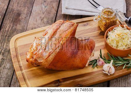 Baked pork shank with sauerkraut on the board