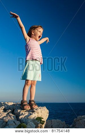 Happy Girl On The Rock With Hands Up