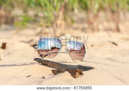 Trendy Sunglasses Lost On The Beach Sand. Outdoors Closeup.