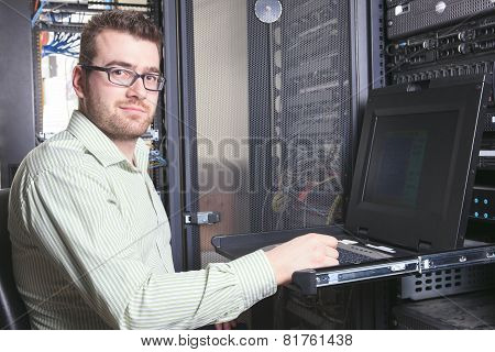 A happy worker technician at work with computer.