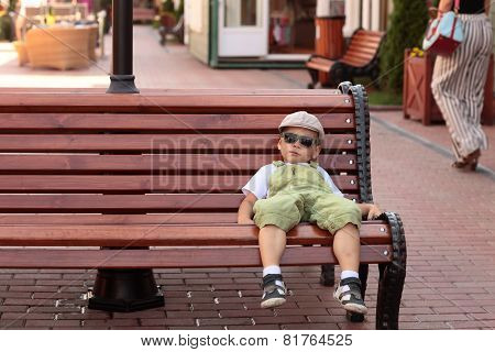 Child Resting On A Bench
