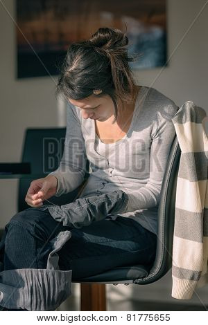Young Mother Repairing Clothes