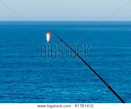 Fishing Bait-rod With Float Against The Blue Sea Water Surface