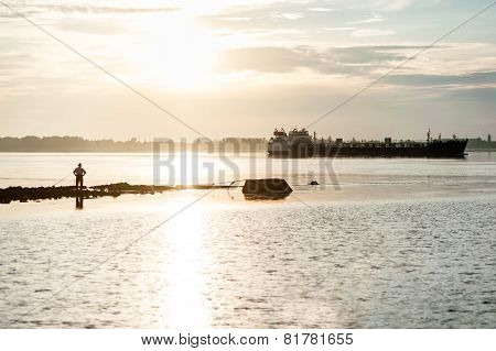 Silhouette Of A Fisherman And A Barge On The River