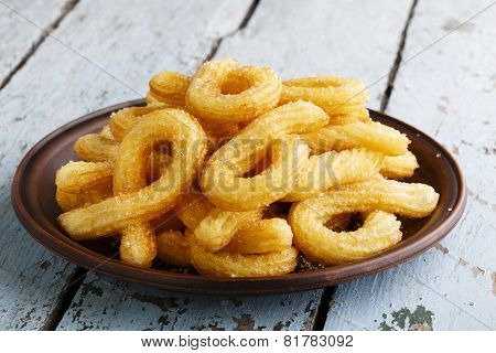 churros sweet dessert with  plate on a wooden surface