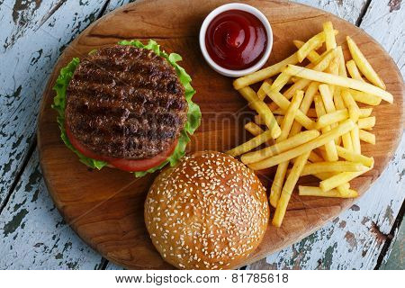 hamburger with french fries and sauce on a wooden surface