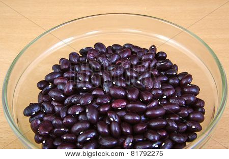 Uncoocked red beans in a cristal bowl on wooden background. Gernika beans.