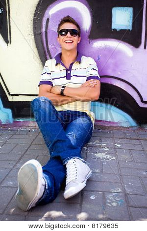 Teenager sitting against graffiti wall