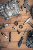 image of carburetor  - Carburetors for a car engine with tools on wooden table - JPG