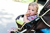 stock photo of finger-licking  - baby girl in the pram licking finger - JPG