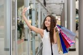 stock photo of mall  - beautiful young woman goes shopping using a smartphone with a shopping bags in the mall - JPG