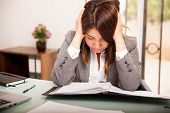 foto of overwhelming  - Portrait of a young business woman stressed and overwhelmed at work - JPG