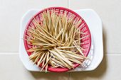 stock photo of gingivitis  - wooden tooth picks in red plastic basket - JPG